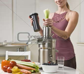 Attractive woman using juicer