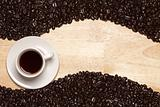 Dark Roasted Coffee Beans and Cup with Saucer on a Wood Textured Background.
