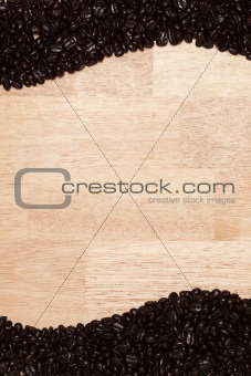 Dark Roasted Coffee Beans on a Wood Textured Background.