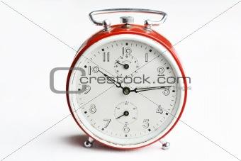 Old red analog alarm clock.