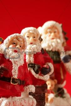 Three Santa Claus figurines over red background, studio