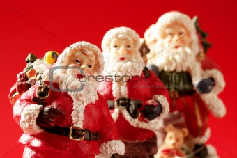 Three Santa Claus figurines over red background, studio