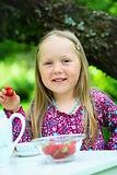 Smiling little girl holding a strawberry at tea party.