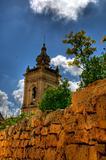 A maltese church tower rising over a stone wall