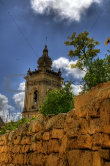 A maltese church tower rising over a stone wall
