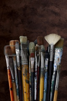 close up of artist paint brushes on dark textured background