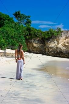 Beautiful brunette walking on beach