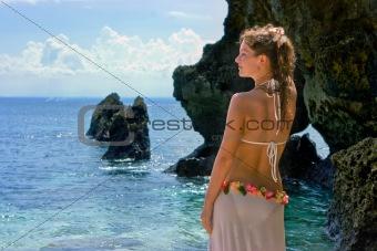 Beautiful brunette on beach half-turned to the sea