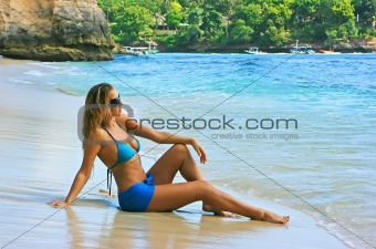 Blonde lady sitting in water on the beach
