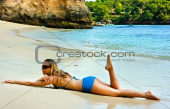 Blonde lady lying in water on the beach