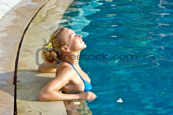 Blonde girl relaxing in hotel pool