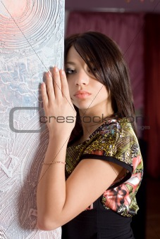 Portrait of the beautiful girl of standing near wall