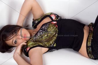 Portrait of the lovely girl lying on a white sofa