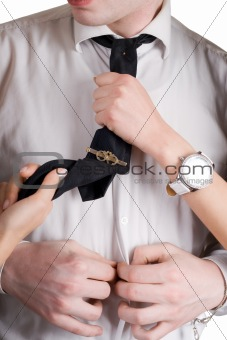 Young man, a tie and female hands. Isolated