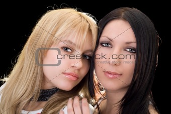 Portrait of the young brunette and blonde. Isolated on black