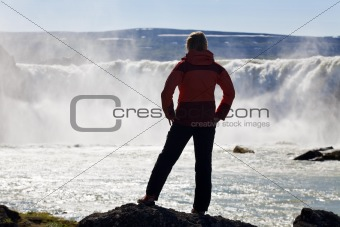 Woman Hiker Stnding In Front Of a Huge Waterfall