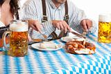 Oktoberfest couple having beer stein and meal