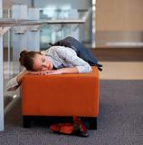 Exhausted young business woman sleeping at work