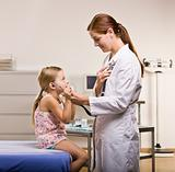 Doctor giving girl checkup in doctorÕs office