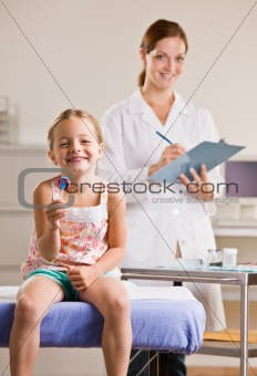 Girl eating lollipop in doctorÕs office