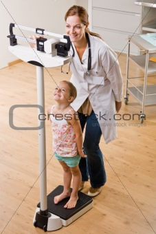 Doctor weighing girl in doctorÕs office