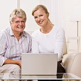 Senior woman and daughter using laptop