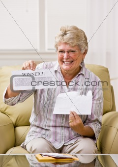 Senior woman holding ÒwinnerÓ notification