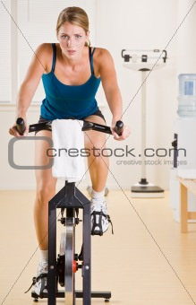 Woman riding stationary bicycle in health club