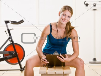 Woman holding stopwatch and clipboard