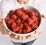 Woman holding bowl of raspberries