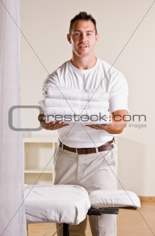 Massage therapist holding stack of towels