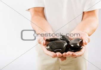 Massage therapist holding warm stones