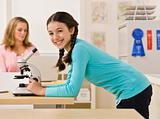 Student looking into microscope in classroom