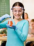 Student holding beaker of liquid in classroom