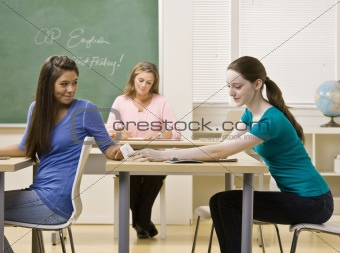 Students passing notes in classroom