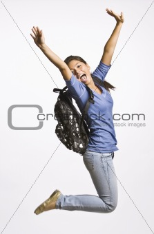 Student wearing backpack jumping