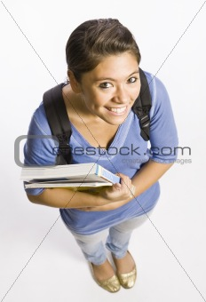 Student wearing backpack carrying books