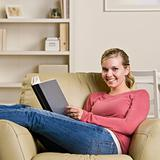 Teenage girl reading book in chair
