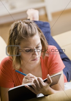 Teenage girl writing in book