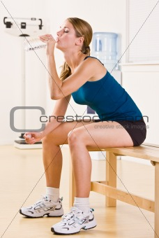 Woman drinking water in health club