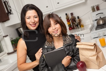Attractive Hispanic Proud Mom with Her Pretty Schoolgirl Daughter in the Kitchen.