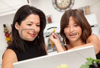 Attractive Hispanic Mother & Daughter in the Kitchen using the Laptop.