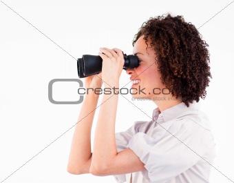 Smiling brunette businesswoman looking through binoculars
