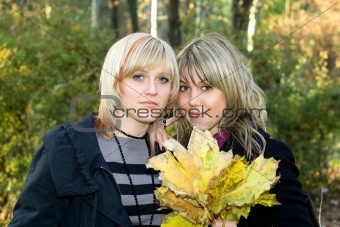 Portrait of the two young women with autumn leaves