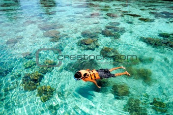 Boy swims on clear crystal ocean