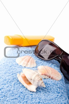 towel, shells, sunglasses and lotion