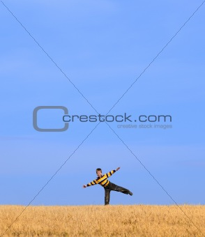 Young boy on field under blue sky