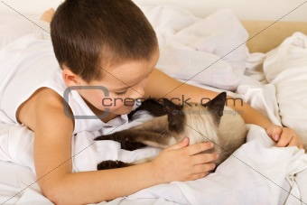 Little boy caressing his kitten in bed