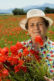 Senior woman picking flowers on the poppy field