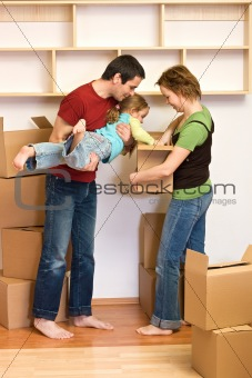 Family unpacking from lots of cardboard boxes